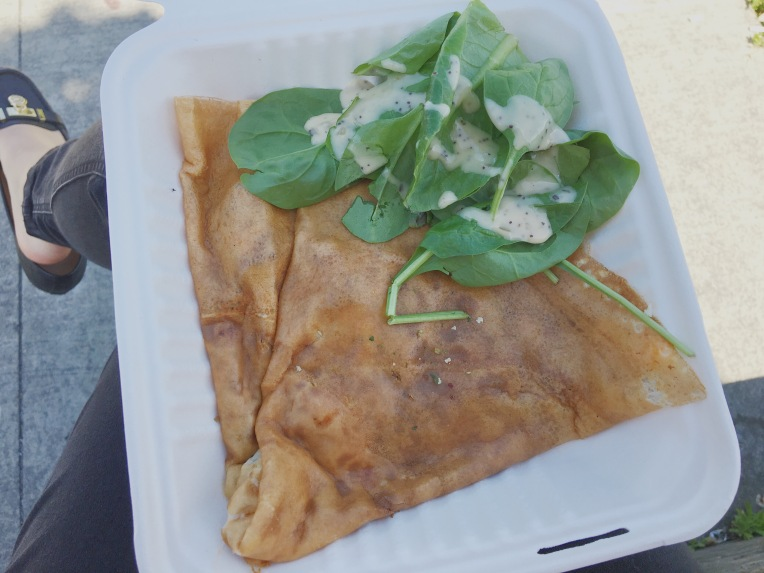 Takeout container with a crepe and a salad.
