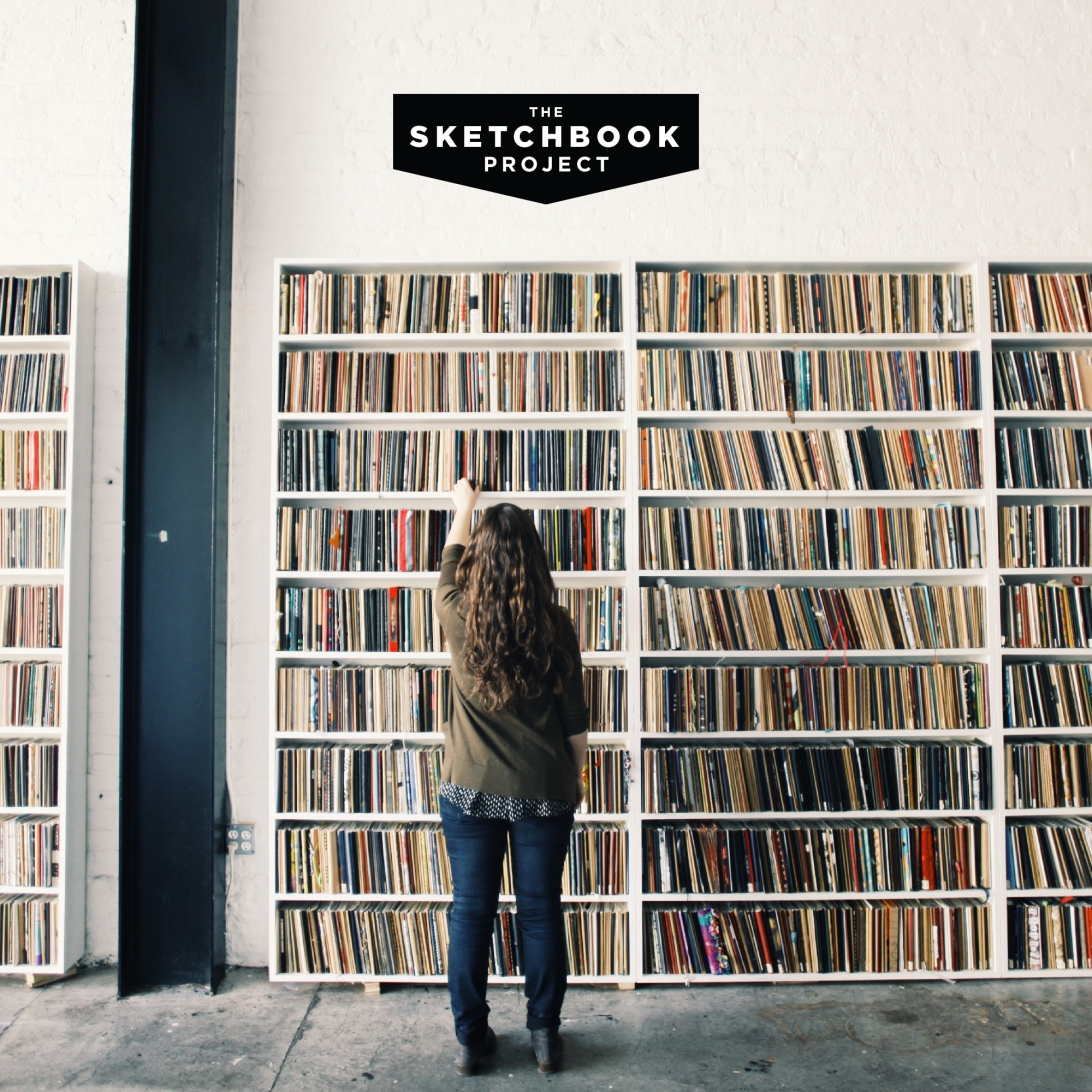 A young person with long hair browses a wall of shelves filled with completed sketchbooks.